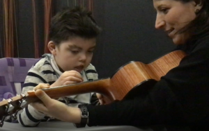 Woman showing child how to play a guitar